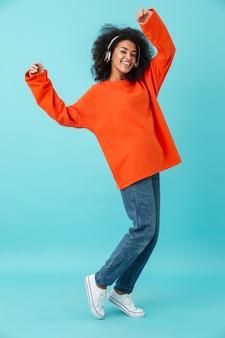 Photo pleine longueur de femme souriante américaine en chemise orange et jeans, écouter de la musique via des écouteurs sans fil, isolé sur mur bleu