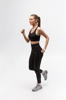 Photo pleine longueur d'une femme sportive qui court en studio