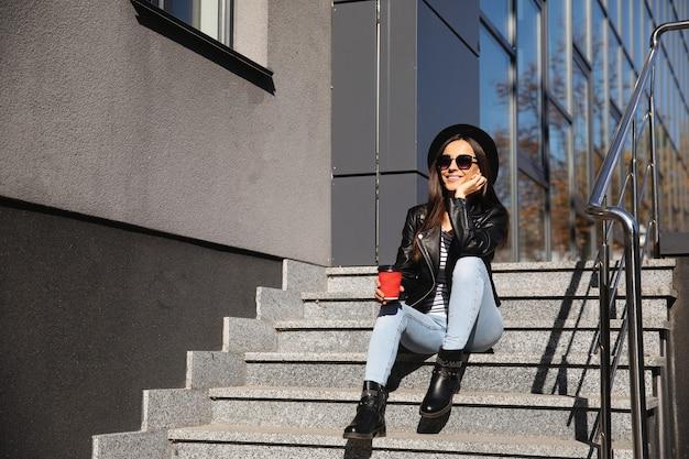 Photo pleine longueur d'une fille adorable dans une tenue à la mode, assise dans les escaliers avec une tasse de café rouge, souriante et rêvant