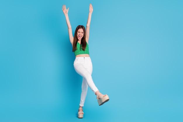 Photo pleine longueur d'une fille candide folle lever les poings crier profiter de vacances de temps libre porter des vêtements de bonne apparence isolés sur fond de couleur bleu