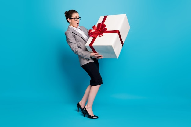 Photo pleine longueur d'une fille de commercialisation étonnée qui porte une veste noire grise isolée sur fond de couleur bleu