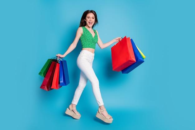 Photo pleine longueur d'une fille énergique qui saute dans de nombreux sacs aime acheter des vêtements hors-vente débardeur en pointillé vert débardeur pantalon blanc pantalon sandales talons hauts isolé fond de couleur bleu