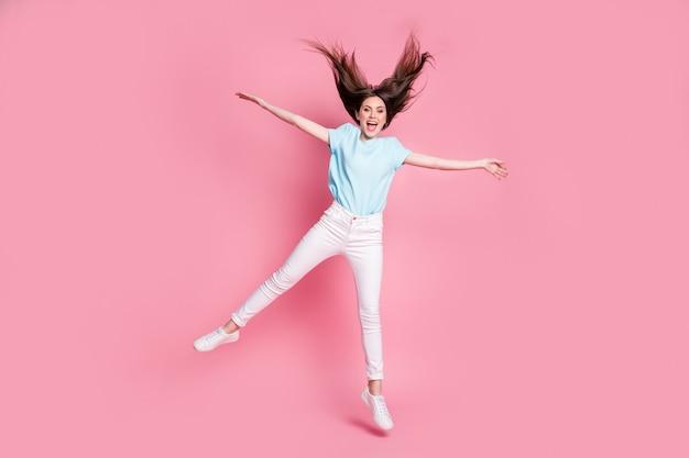Photo pleine longueur d'une fille étonnée qui saute porter des vêtements de bonne humeur isolés sur fond de couleur rose