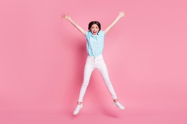 Photo pleine longueur d'une fille folle et insouciante qui saute les mains isolées sur fond de couleur rose