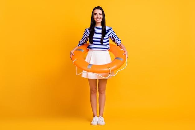 Photo pleine longueur d'une fille joyeuse et positive profiter de l'eau dans l'océan et avoir une bouée de sauvetage en caoutchouc portant une tenue bleue isolée sur fond de couleur brillante et brillante