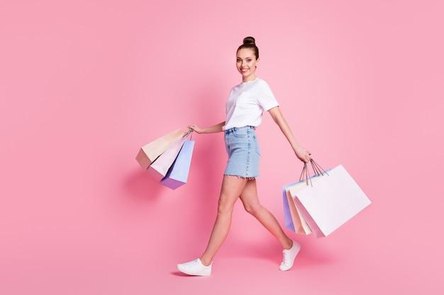Photo pleine longueur d'une fille joyeuse et positive qui aime faire du shopping soulever de nombreux sacs