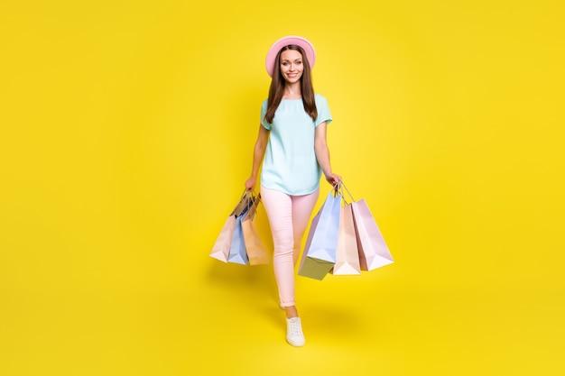 Photo pleine longueur fille positive centre commercial client profiter du repos se détendre aller marcher centre commercial acheter des ventes tenir des sacs porter un chapeau de soleil rose bleu élégant baskets à la mode isolé fond de couleur brillant brillant