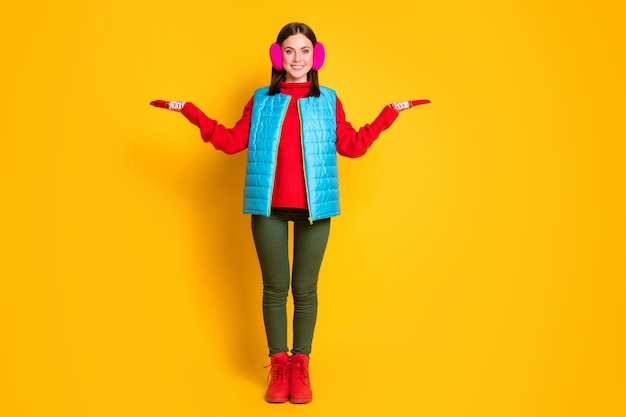 Photo pleine longueur fille positive tenir la main démontrer publicité promo présente vendredi noir choix décision conseil porter bleu vert rose pull bottes isolé brillant fond de couleur