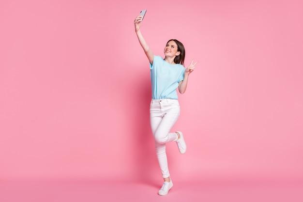 Photo pleine longueur de fille sauter utiliser smartphone prendre selfie faire v-sign porter un t-shirt pantalon isolé fond de couleur pastel