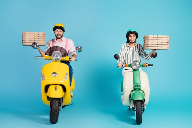 Photo pleine longueur de funky crazy lady guy conduire deux vélomoteurs vintage transporter des boîtes à pizza occupation de courrier indésirable fast-food formalwear tenue casque de protection mur de couleur bleu isolé