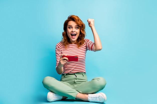 Photo pleine longueur funky impressionné femme assis plancher jambes croisées utilisation smartphone gagner en ligne loterie réseau social lever les poings crier wow porter vert élégant cavalier isolé couleur bleu