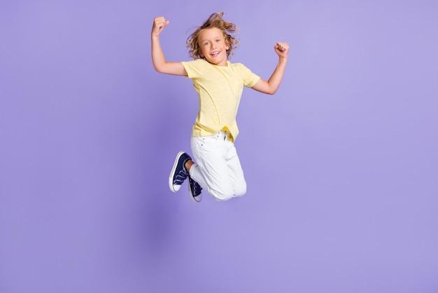 Photo pleine longueur d'un garçon positif montrant des biceps portant un t-shirt jaune blanc isolé sur fond de couleur violet