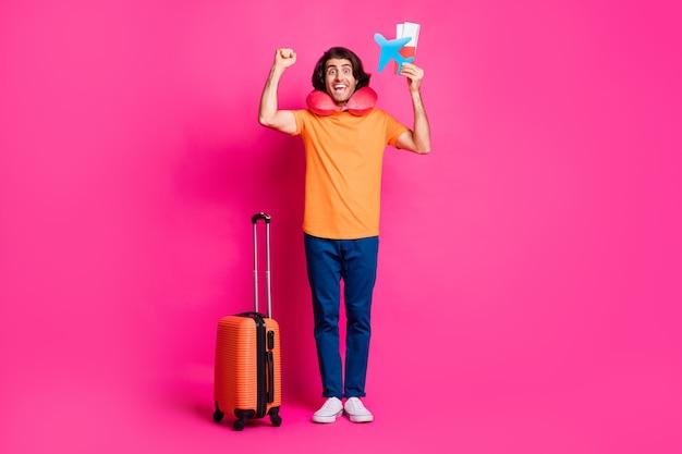 Photo pleine longueur de gars bagages billets avion en papier lever poing porter coussin de cou t-shirt orange jeans baskets isolé fond de couleur rose vif