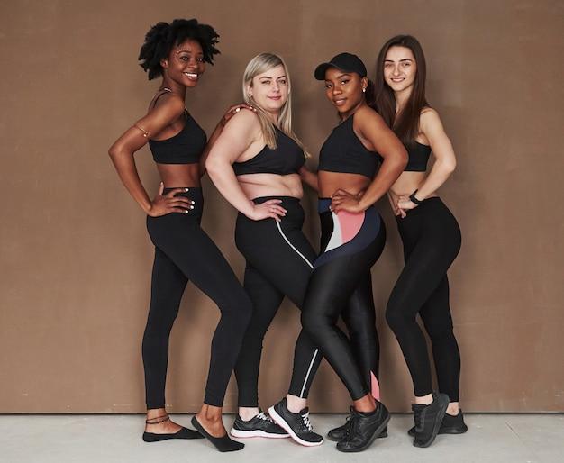 Photo pleine longueur. groupe de femmes multiethniques debout contre l'espace brun