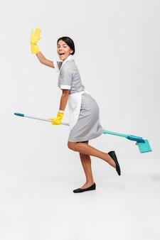 Photo pleine longueur de happy funny girl in uniform riding mop comme une sorcière