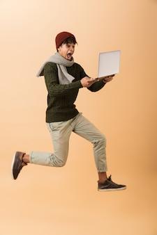Photo pleine longueur d'un homme afro-américain excité portant un chapeau et un foulard marchant avec un ordinateur portable, isolé sur un mur beige
