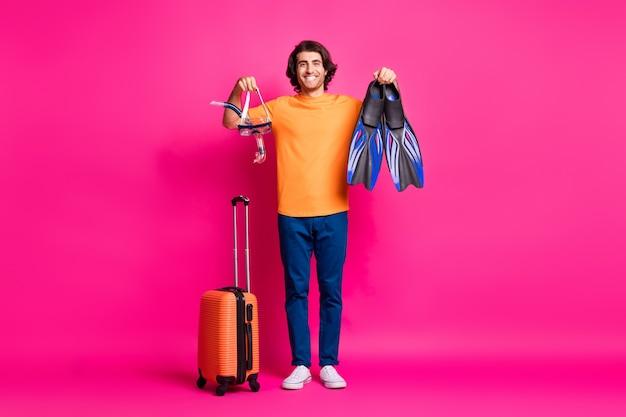Photo pleine longueur de l'homme bagages tenir le masque flips porter des baskets jeans t-shirt orange isolé fond de couleur rose
