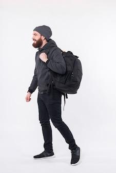 Photo pleine longueur d'un homme barbu marchant sur blanc avec sac à dos