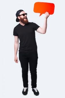 Photo pleine longueur d'un homme barbu regardant une bulle de dialogue rouge sur blanc