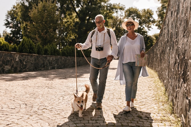 Photo pleine longueur de l'homme en chemise blanche et jeans avec appareil photo et femme au chapeau et chemisier bleu rayé avec carte et corgi marchant dans le parc.