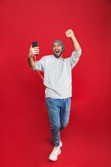Photo pleine longueur de l'homme européen 30s chantant tout en écoutant de la musique avec des écouteurs et un téléphone mobile, isolé