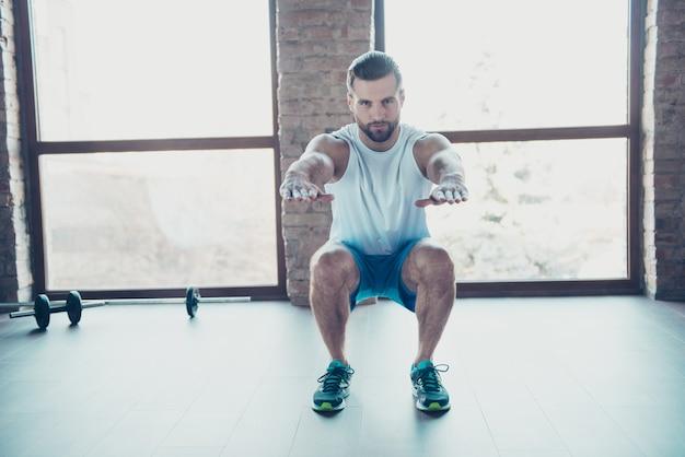 Photo pleine longueur d'un homme macho faisant des squats statiques vêtements de sport brûlant de la graisse débardeur blanc short bleu baskets formation à la maison près de grandes fenêtres à l'intérieur