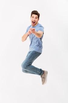 Photo pleine longueur d'homme positif en t-shirt décontracté et jeans sautant et pointant le doigt sur la caméra, isolé sur mur blanc