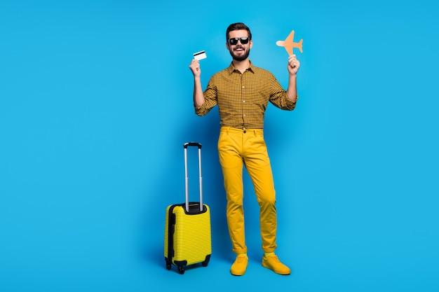 Photo pleine longueur homme positif touristique tenir carte de dépôt avion papercard payer sans fil facile à faible coût week-end repos voyage porter des pantalons à carreaux style élégant briller branché isolé couleur bleu