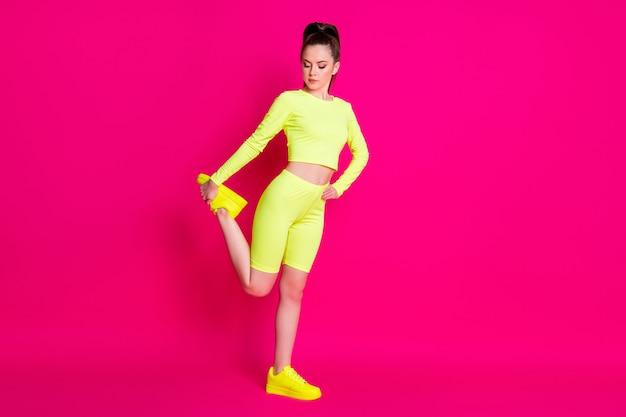 Photo pleine longueur de la jambe extensible de la sportive porter des shorts de baskets jaunes isolés sur fond de couleur rose vif