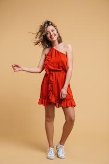 Photo pleine longueur d'une jeune femme blonde de 20 ans vêtue d'une robe rouge souriante et posée isolée sur un mur beige
