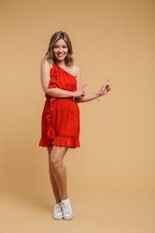 Photo pleine longueur d'une jeune femme européenne de 20 ans vêtue d'une robe rouge souriante et pointant du doigt le fond isolé sur un mur beige