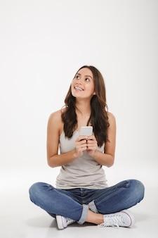 Photo pleine longueur de jeune femme en jeans et baskets assis avec les jambes croisées sur le sol avec un smartphone en argent à la main, sur un mur blanc