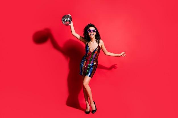 Photo pleine longueur de jeune femme tenir boule disco porter des lunettes de soleil star mini robe brillante talons hauts isolé fond de couleur rouge