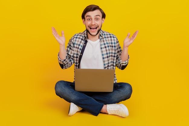 Photo pleine longueur d'un jeune homme heureux tenant un ordinateur portable étonné des nouvelles excitées assis sur un sol isolé sur fond de couleur jaune