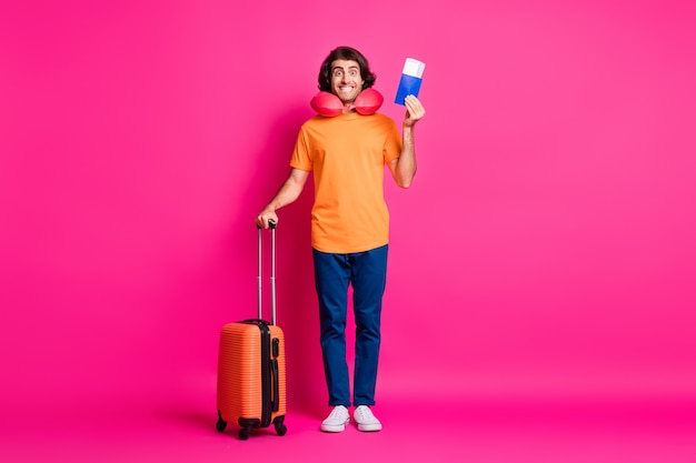 Photo pleine longueur d'un jeune homme tenant des billets de cas passeport porter un coussin de cou t-shirt orange jeans baskets isolé fond de couleur rose