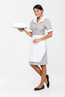 Photo pleine longueur de jeune jolie femme en uniforme tenant un plateau en métal avec une carte de signe vide en position debout