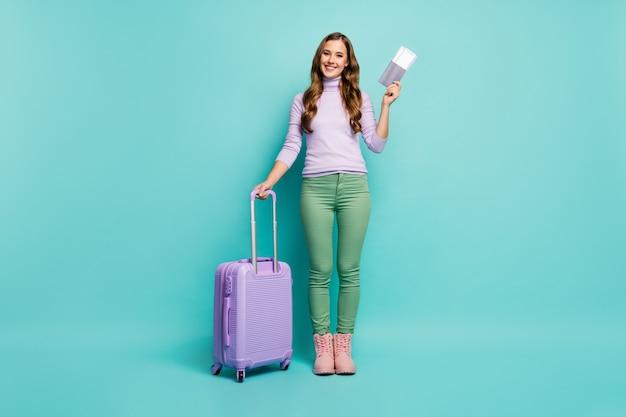 Photo pleine longueur de la jolie dame des documents de l'aéroport enregistrement tenir des billets de voyage roulant valise porter pull lilas pantalon vert chaussures isolé couleur pastel sarcelle