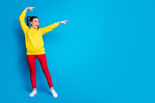 Photo pleine longueur de jolie dame drôle deux queues doigts directs côté espace vide vente shopping bannière porter décontracté pull à capuche jaune pantalon rouge isolé fond de couleur bleu vif
