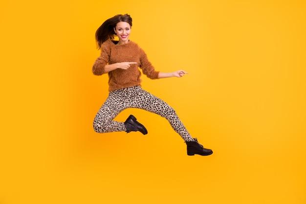 Photo pleine longueur de jolie dame drôle sauter haut indiquant les doigts de l'espace vide conseillant les ventes de la saison finale