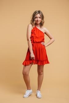 Photo pleine longueur d'une jolie femme blonde de 20 ans vêtue d'une robe rouge souriante et posée isolée sur un mur beige
