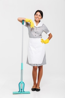 Photo pleine longueur d'une jolie femme de chambre brune en uniforme s'appuyant sur une vadrouille en position debout