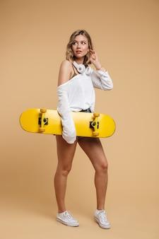 Photo pleine longueur d'une jolie femme européenne portant un short en jean avec des écouteurs et une planche à roulettes isolée sur un mur beige
