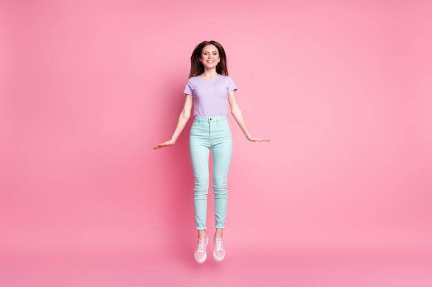 Photo pleine longueur d'une jolie fille charmante qui saute profiter du repos du printemps se détendre porter des vêtements de bonne apparence, des chaussures en caoutchouc isolées sur un fond de couleur rose