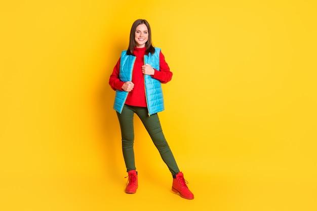 Photo pleine longueur d'une jolie jeune femme magnifique souriante posant une veste zippée par temps froid et venteux porter un pantalon vert gilet bleu pull rouge bottes isolées fond de couleur jaune vif
