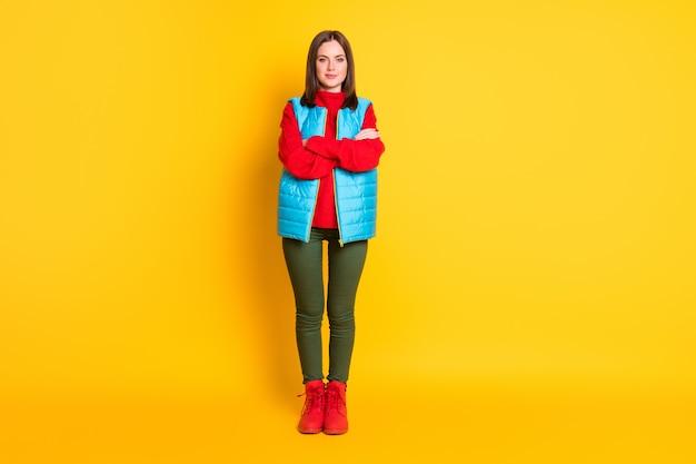 Photo pleine longueur d'une jolie jeune femme souriante, mains croisées, regard sûr de soi, attente d'un pantalon vert, gilet bleu, pull rouge, bottes isolées, fond de couleur jaune vif