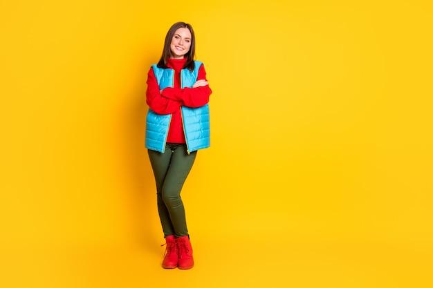 Photo pleine longueur d'une jolie jeune femme souriante, mains pliées, regard assuré en attente de temps de ski porter un pantalon vert gilet bleu pull rouge bottes isolées fond de couleur jaune vif