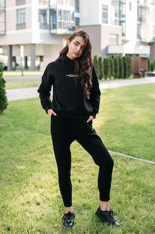 Photo pleine longueur d'une jolie jeune femme en tenue de sport noire posant dans la rue en se tenant debout sur la pelouse à l'extérieur. mode féminine. mode de vie en ville
