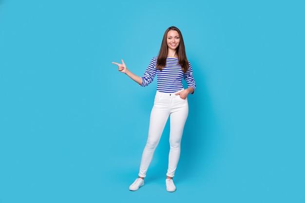 Photo pleine longueur d'une jolie jeune fille en forme de poche pour la main dirigeant l'espace vide du doigt proposer un voyage à l'étranger porter une chemise rayée pantalon blanc baskets isolé fond de couleur bleu vif
