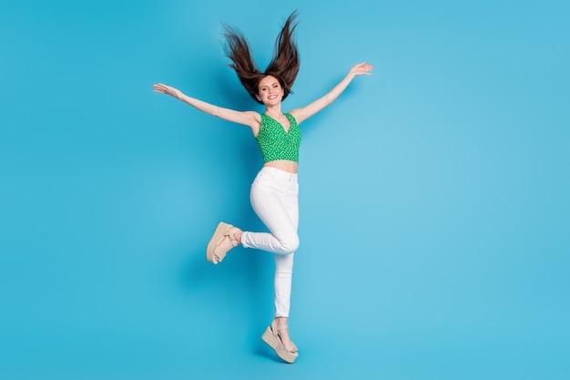 Photo pleine longueur d'une jolie jolie fille charmante qui saute profiter d'une coupe de cheveux à la mouche de l'air tenir lever les mains porter une tenue de bonne apparence isolée sur fond de couleur bleu