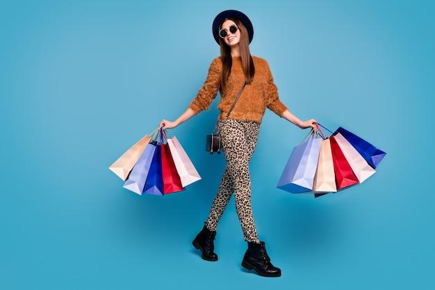 Photo pleine longueur de joyeuse boutique client fille voyage touristique automne automne printemps week-ends tenir des sacs porter des pantalons pull marron bottes lunettes de soleil mur de couleur bleu isolé